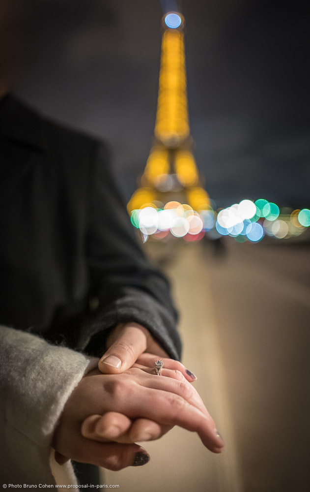 proposal focus ring hand in hand front the Eiffel Tower at night