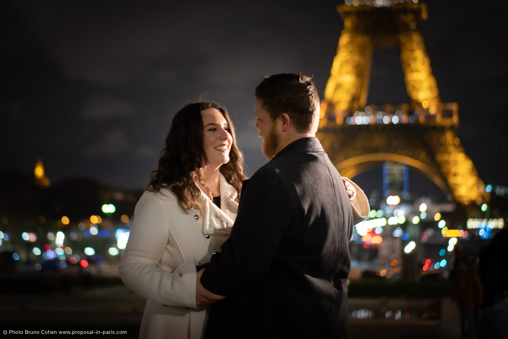 couple in love look at each other front of Eiffel Tower at night