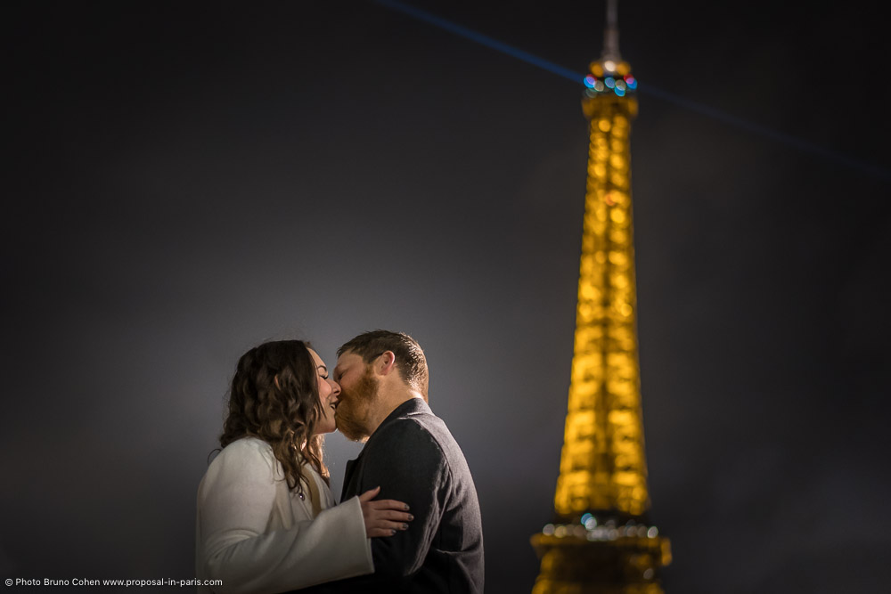 kissing couple standing front of Eiffel Tower at night