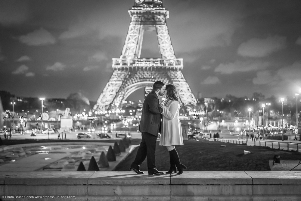 couple kissing front the Eiffel Tower at night in black and white