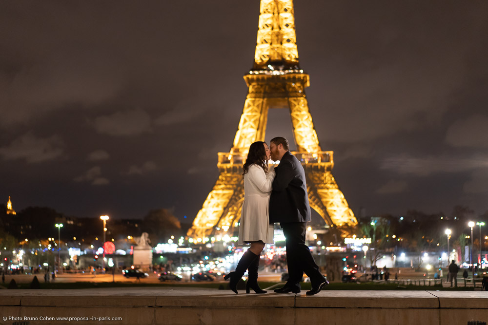 couple kissing front the Eiffel Tower at night