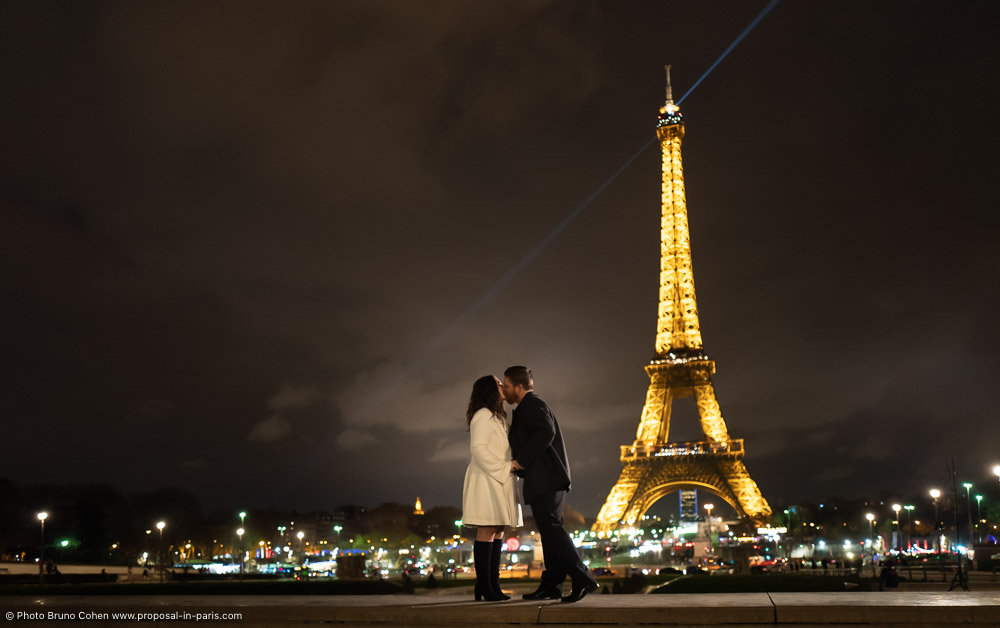 couple hand in hand standing front of Eiffel Tower at night