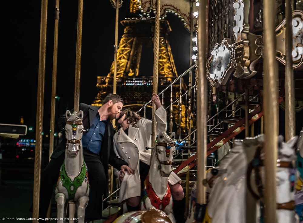 couple kiss riding a carousel horse in paris front Eiffel Tower at night