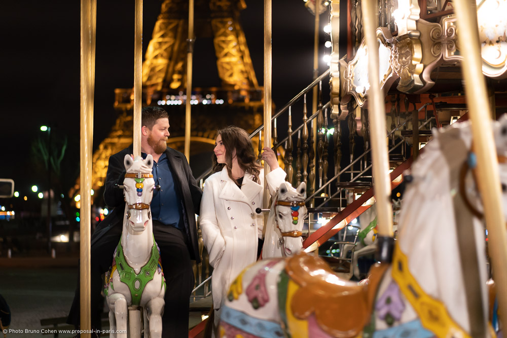 couple look at each other riding a carousel horse in paris front Eiffel Tower at night