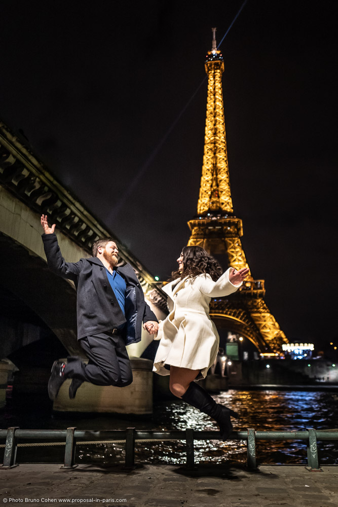 couple jumping front Eiffel Tower at night