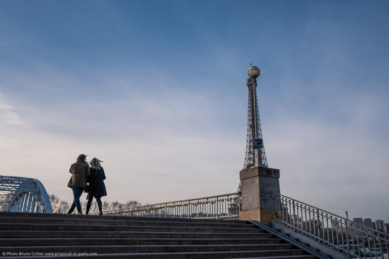 couple walk on a bridge front of Eiffel Tower