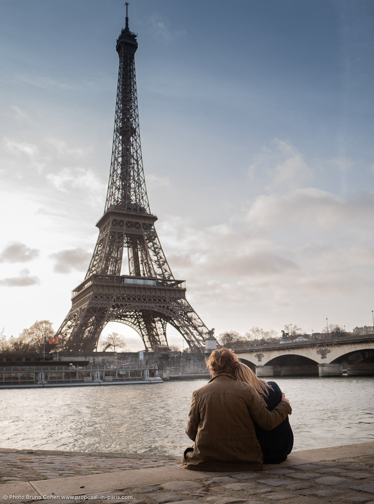couple sitting on the quai de seine and looking the Eiffel Tower at the sunrise