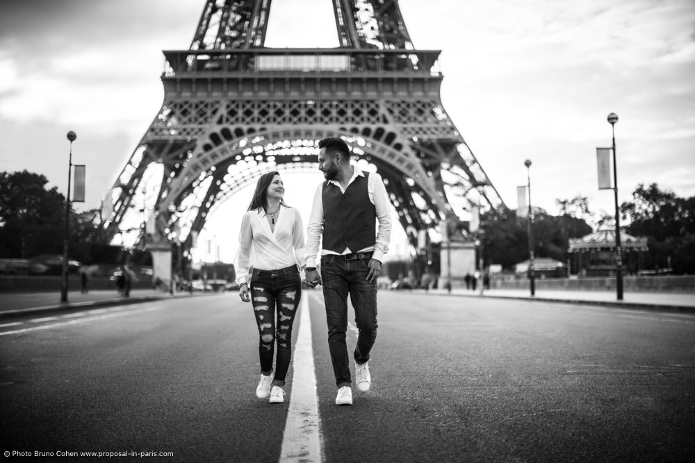 portrait of a walking couple holding hands on the road in paris in black and white