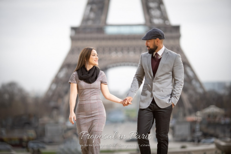 young couple walking in front of the Eiffel Tower Paris
