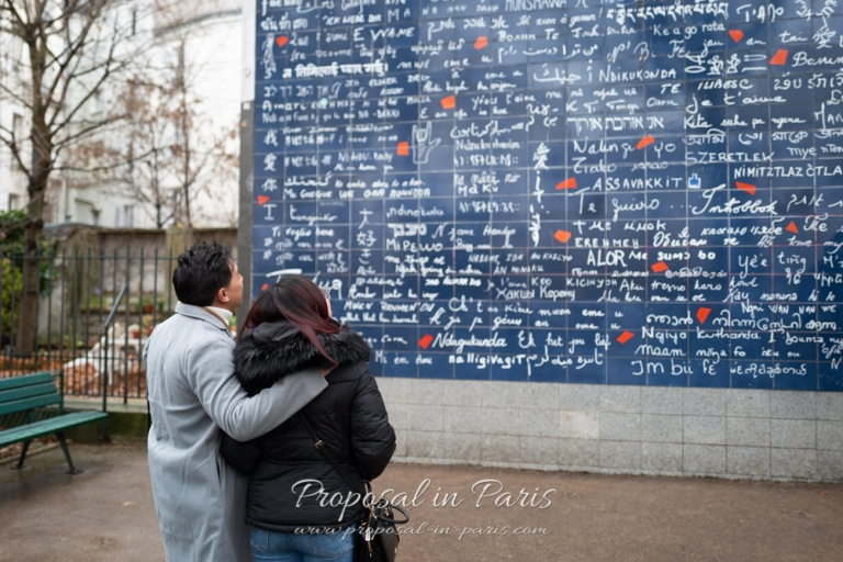 couple looking at the Love Wall in Montmartre Paris