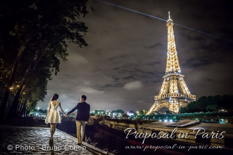 a couple is walking along the Seine river by night near the Eiffel Tower