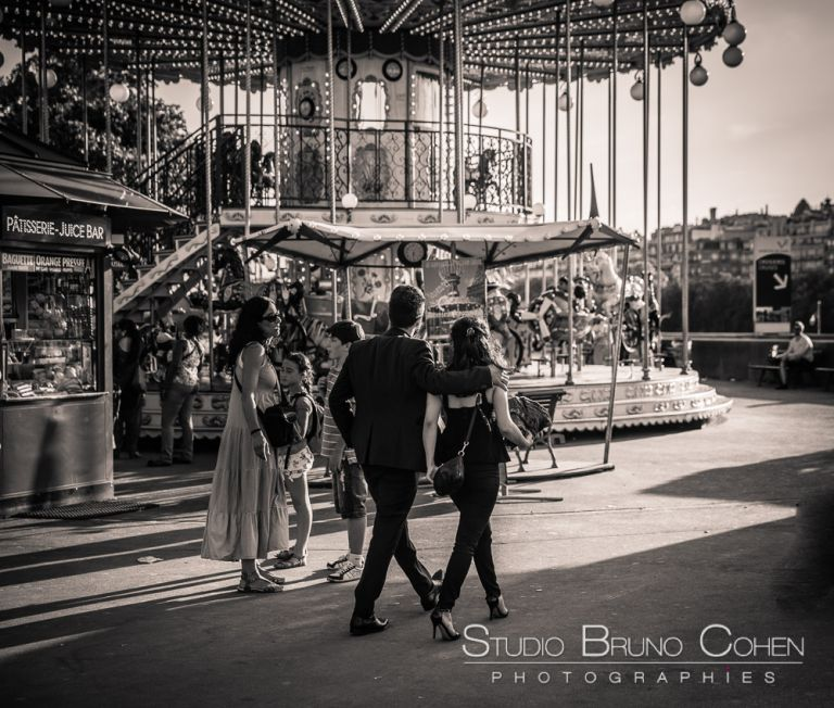 proposal in paris hidden photographer couple walk front of eiffel tower carousel black an white