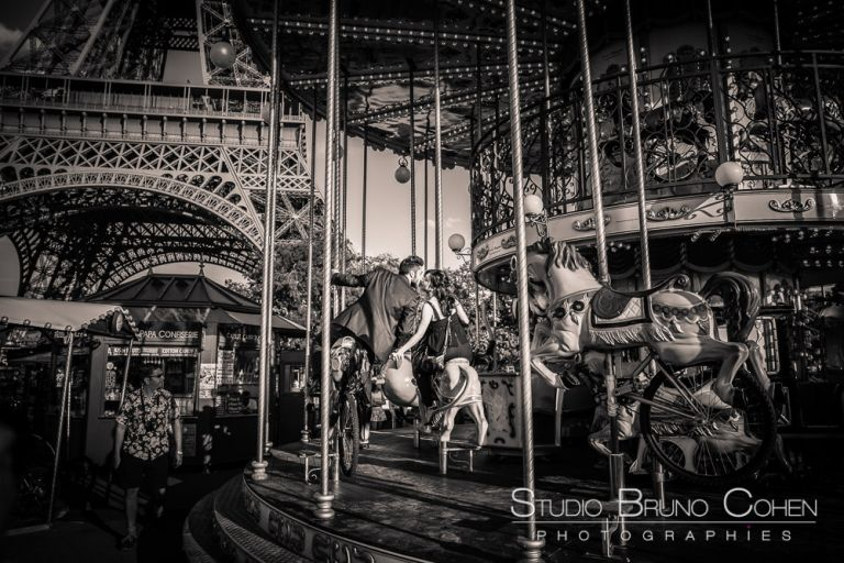 proposal in paris kissing couple ride horses on carousel front of eiffel tower black and white summer