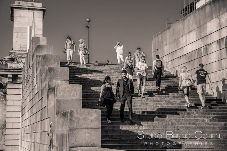 portrait couple hand in hand downstrairs in paris from quai de seine near eiffel tower proposal surprise love kiss black and white