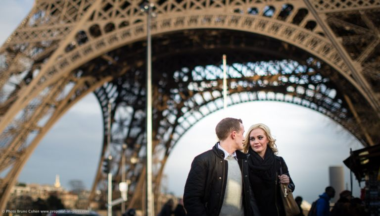 couple walk in paris front of Eiffel Tower proposal love
