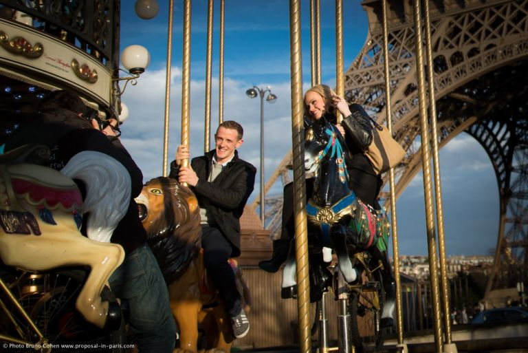 couple ride on horses from Eiffel Tower carousel in paris happy