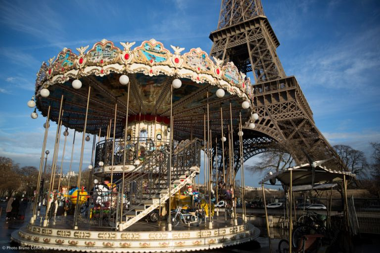 proposal in paris carousel front of Eiffel Tower blue sky