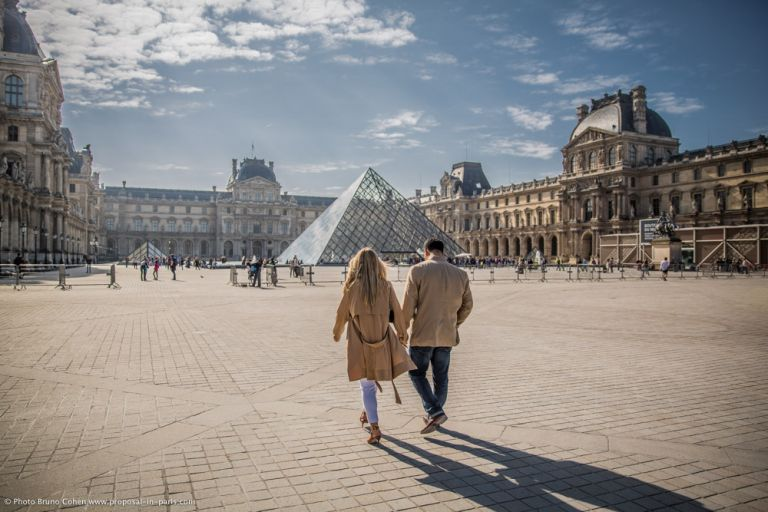 couple hand in hand walking in paris at louvres pyramid