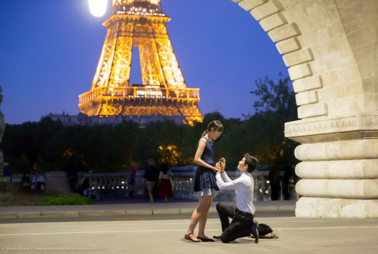 surprise proposal in paris by night front of Eiffel Tower from Bir Hakeim bridge