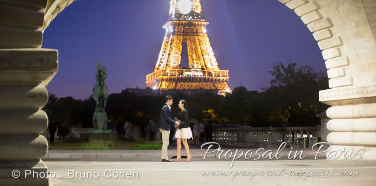 couple face to face from Bir Hakeim bridge front of Eiffel Tower by night in paris