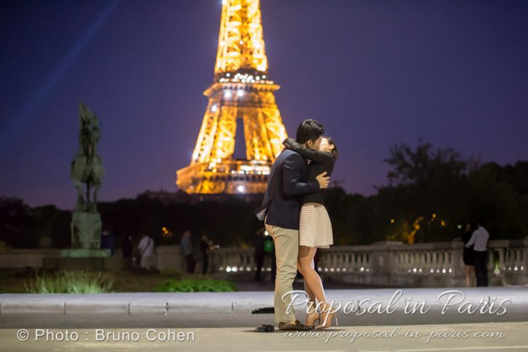 kissing couple from Bir Hakeim bridge front of Eiffel Tower sparkles by night proposal