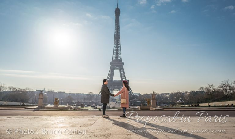 Eiffel Tower at sunrise with a couple holding hands