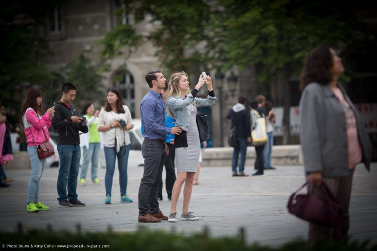 portrait couple taking photo from notre dame cathedral in paris