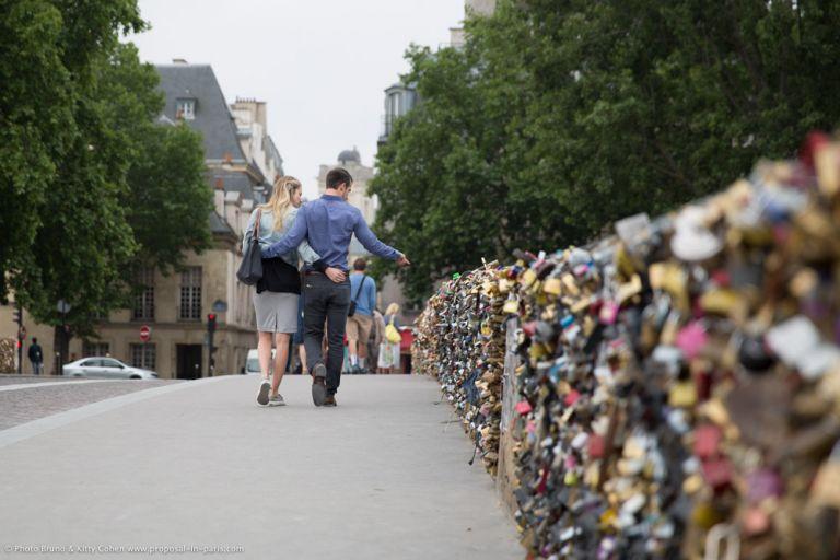 portrait couple walking from lock bridge in paris with love